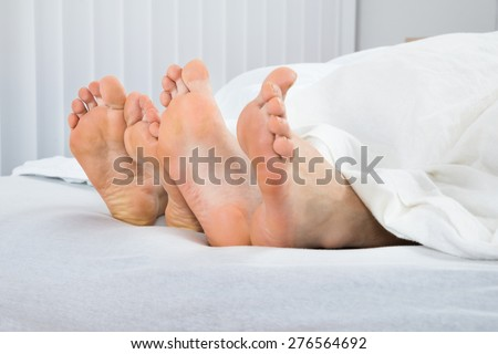 Close-up Of Four Feet In White Bed