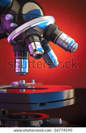 Close up of four lens microscope turret on orange background