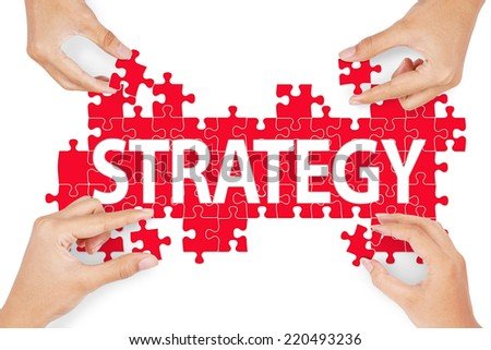 Close up of four people hands with puzzle making strategy word - stock photo
