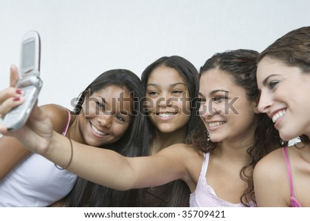 Close-up of four teenage girls taking a picture of themselves with a mobile phone and smiling - stock photo