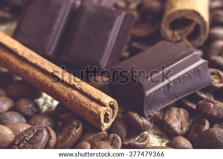Close-up of fragrant cinnamon sticks and chocolate blocks with blured coffee beans as background. Selective focus. - stock photo