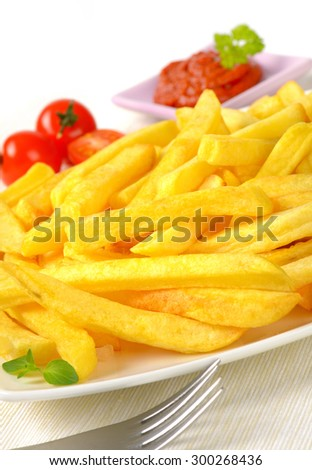 close up of french fries and silver fork on white plate - stock photo
