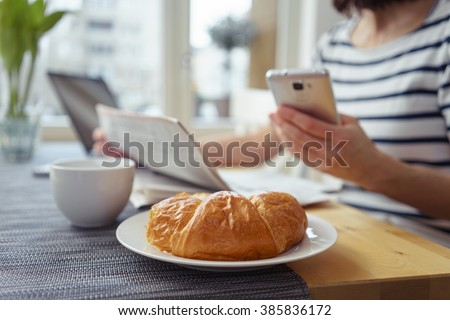 Close Up of Fresh Baked Croissant on Kitchen Table with Coffee Mug in front of Unrecognizable Woman Reading Newspaper and Checking Cell Phone Messages on Relaxing Morning at Home - stock photo