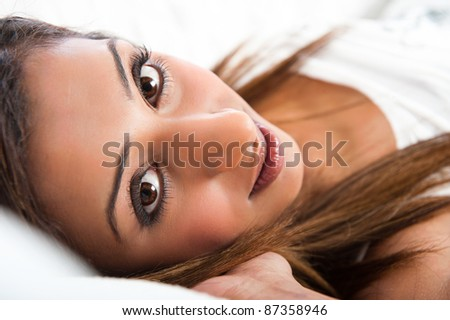 Close-up of fresh beautiful young Asian Indian model, lying down with hand in hair - stock photo