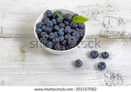 Close up of fresh blueberries, inside and outside of bowl, on rustic white wooden table.