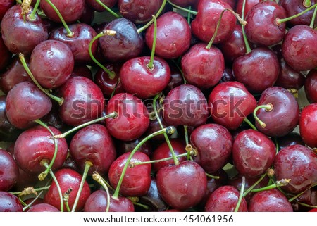 Close up of fresh cherry berries with water drops as background. Tasty red cherry background. Summer fruits background with fresh cherry. Sour cherries background. Pile of cherries background texture. - stock photo