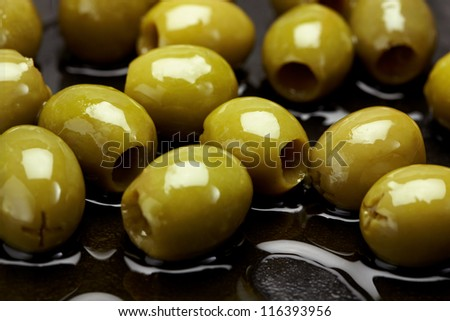 Close up of fresh green olives in oil - stock photo