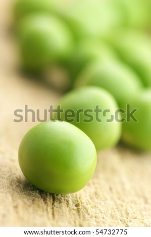 Close-up of fresh green peas on wooden board. - stock photo