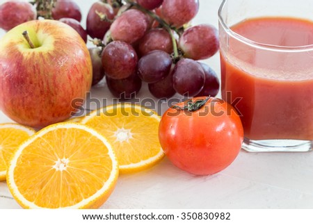Close up of fresh juice glass and fruits on table - healthy eating - stock photo