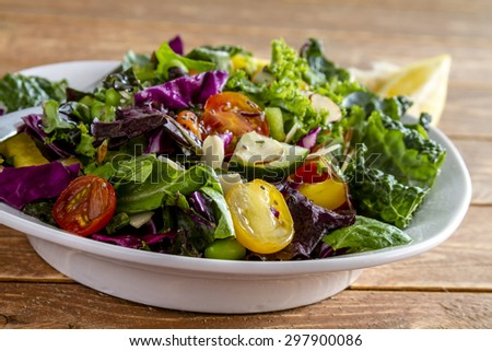 Close up of fresh organic super food salad in white bowl sitting on wooden table - stock photo
