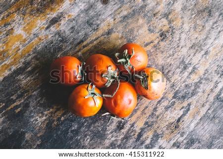 Close-up of fresh, ripe tomatoes on wood background - stock photo