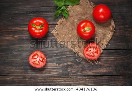 Close-up of fresh, ripe tomatoes on wood background. - stock photo