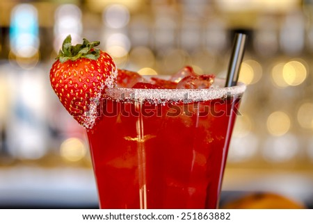 Close up of fresh strawberry vodka cocktail with ice and sugar on glass rim garnished with fresh strawberry sitting on bar with napkin and hamburger sliders in background - stock photo