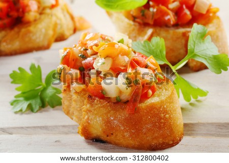Close Up of Fresh Tomato Bruschetta Appetizers on Crisp Crusty French Baguette Bread Slices Garnished with Fresh Herbs on White Wooden Table Surface - stock photo