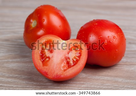 Close up of fresh tomatoes in drops of water on a wooden board