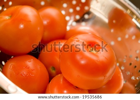 Close-up of fresh tomatos in silver strainer - stock photo