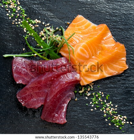 Close up of fresh tuna and salmon sashimi on black plate. - stock photo