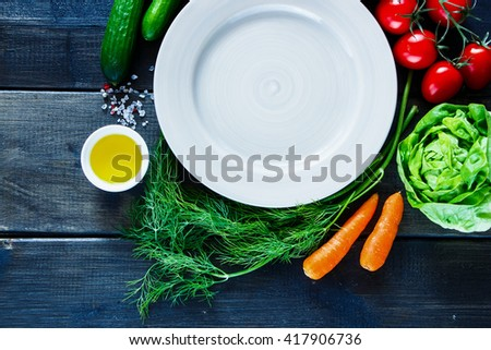 Close up of fresh vegetables for tasty vegan and diet cooking or salad making around empty plate on rustic wooden background, top view. Vegetarian food concept. - stock photo