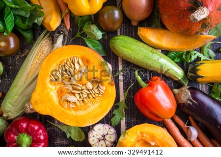 Close up of fresh vegetables on a rustic dark table. Autumn background. Healthy eating. Sliced pumpkin, zucchini, squash, bell peppers, carrots, onions, cut garlic, tomatoes, eggplant. Top view - stock photo