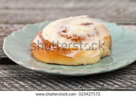 Close up of freshly baked homemade cinnamon roll with cream cheese buttercream frosting and an antique bottle of milk - stock photo