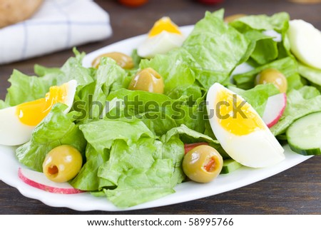 Close up of freshly made salad with lettuce,eggs and olives - stock photo