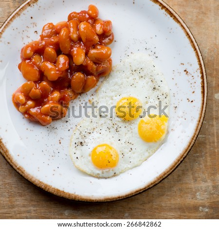 Close-up of fried quail eggs with beans, view from above - stock photo