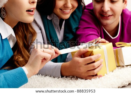 Close-up of friends lying on the floor and unwrapping small giftbox - stock photo