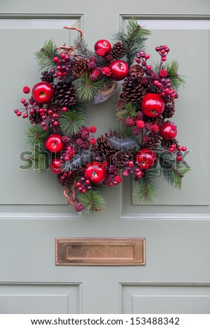 Close-up of fruit themed Christmas wreath on a pale green door. - stock photo