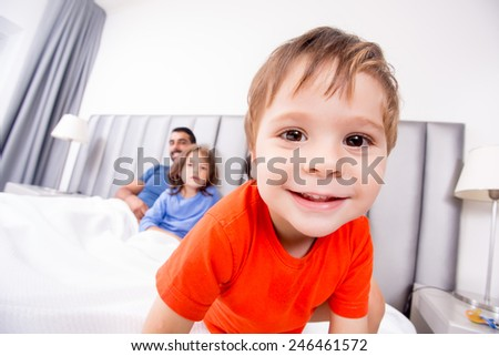 Close up of funny boy playing in bed with family - stock photo