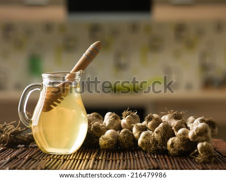 close-up of garlic and jug with honey and dipper, on wooden kitchen table - stock photo