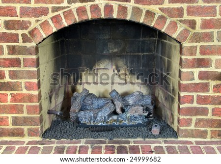 Close up of gas fireplace surrounded with brick. - stock photo