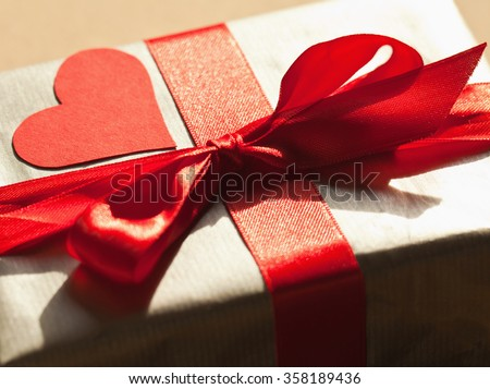 Close up of gift box wrapped in silver paper with red bond and red heart. Selective focus, copy space.