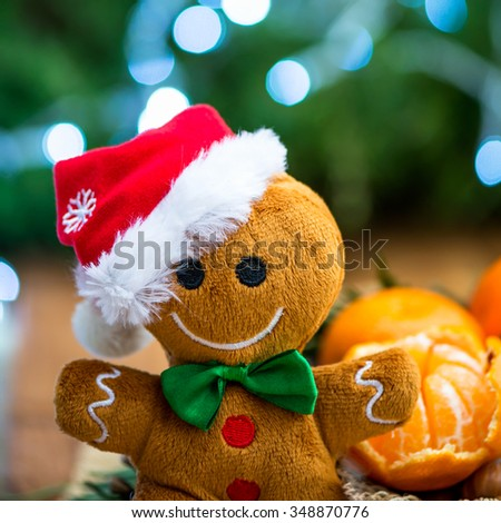 Close Up of Gingerbread Man Soft Toy and Peeled Fresh Clementine or Tangerine with Xmas Lights and Tree Branches on the Background