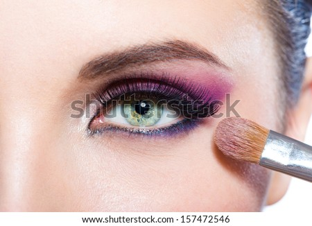 Close up of girl applying bright pink makeup on eye with brush - stock photo