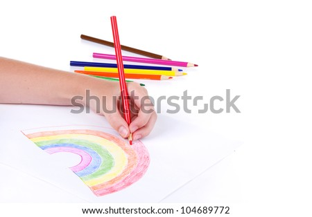 Close-up of girl drawing a rainbow with colored pencils - stock photo