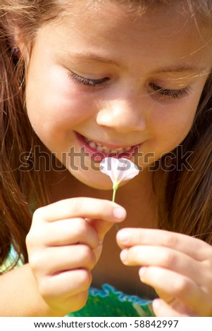 Close-up of girl enjoying nice smell of tiny flower - stock photo