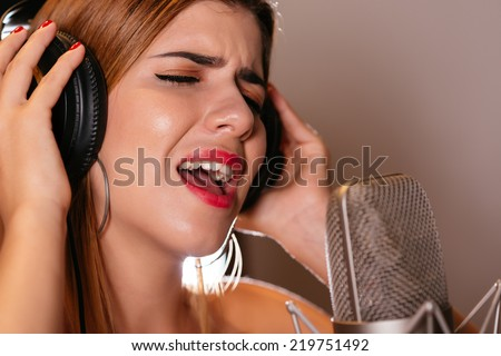 Close-up of girl in headphones singing a song - stock photo