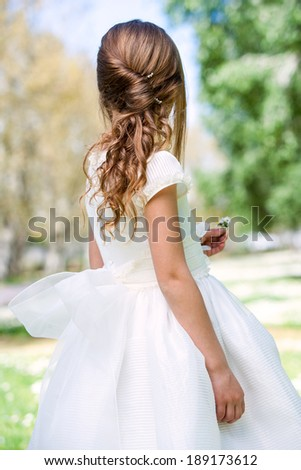 Close up of girl in white dress showing hairstyle outdoors. - stock photo