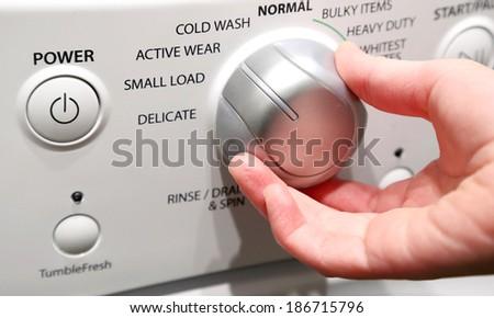 Close up of girl's hand adjusting washing machine  - stock photo