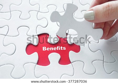Close up of girl's hand placing the last jigsaw puzzle piece with word Benefits - stock photo