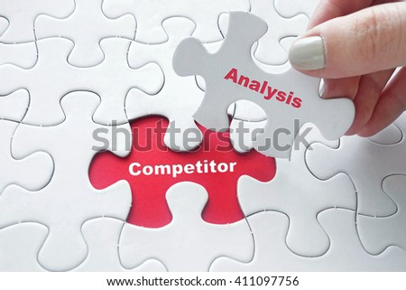 Close up of girl's hand placing the last jigsaw puzzle piece with word Competitor Analysis as business concept