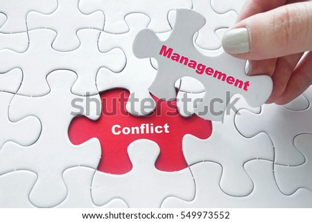 Close up of girl's hand placing the last jigsaw puzzle piece with word Conflict Management