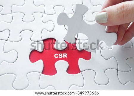 Close up of girl's hand placing the last jigsaw puzzle piece with word CSR ( Corporate Social Responsibility )