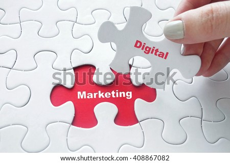 Close up of girl's hand placing the last jigsaw puzzle piece with word Digital Marketing as business concept