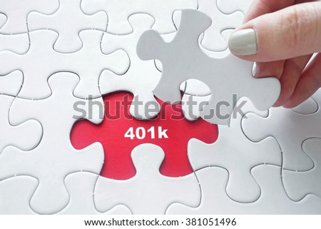 Close up of girl's hand placing the last jigsaw puzzle piece with word 401k. It is retirement savings plan sponsored by employer