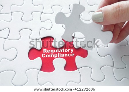 Close up of girl's hand placing the last jigsaw puzzle piece with word Regulatory Compliance - stock photo