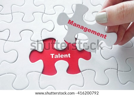 Close up of girl's hand placing the last jigsaw puzzle piece with word Talent Management - stock photo