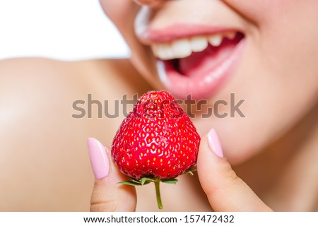 Close up of girl's mouth eating strawberry, isolated on white. Concept of beauty and healthy food