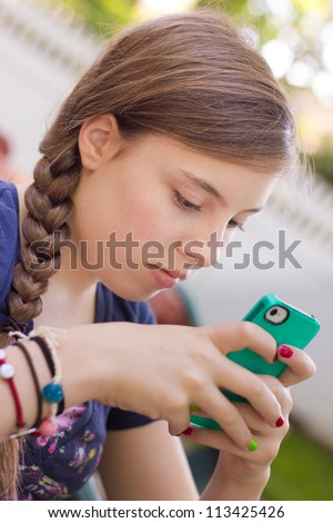 Close-up of girl texting on her handheld mobile cell phone while sitting outside - stock photo