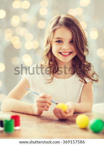 close up of girl with brush coloring easter eggs - stock photo